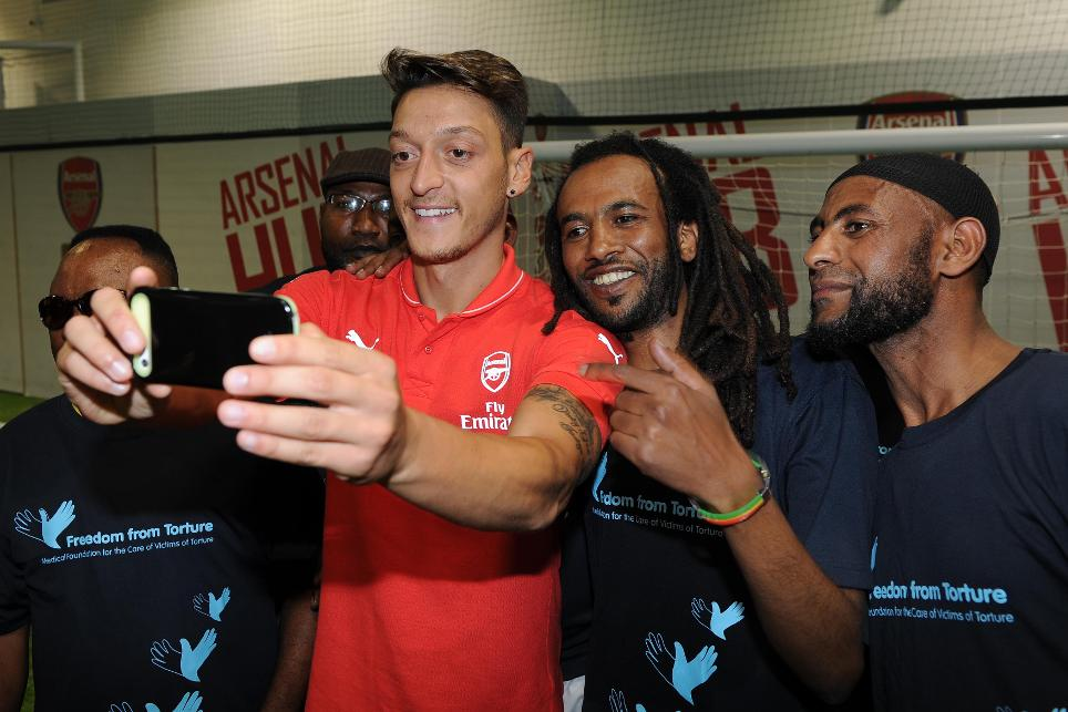 Arsenal's Mesut Ozil with members of the Freedom from Torture group at Arsenal's Hub