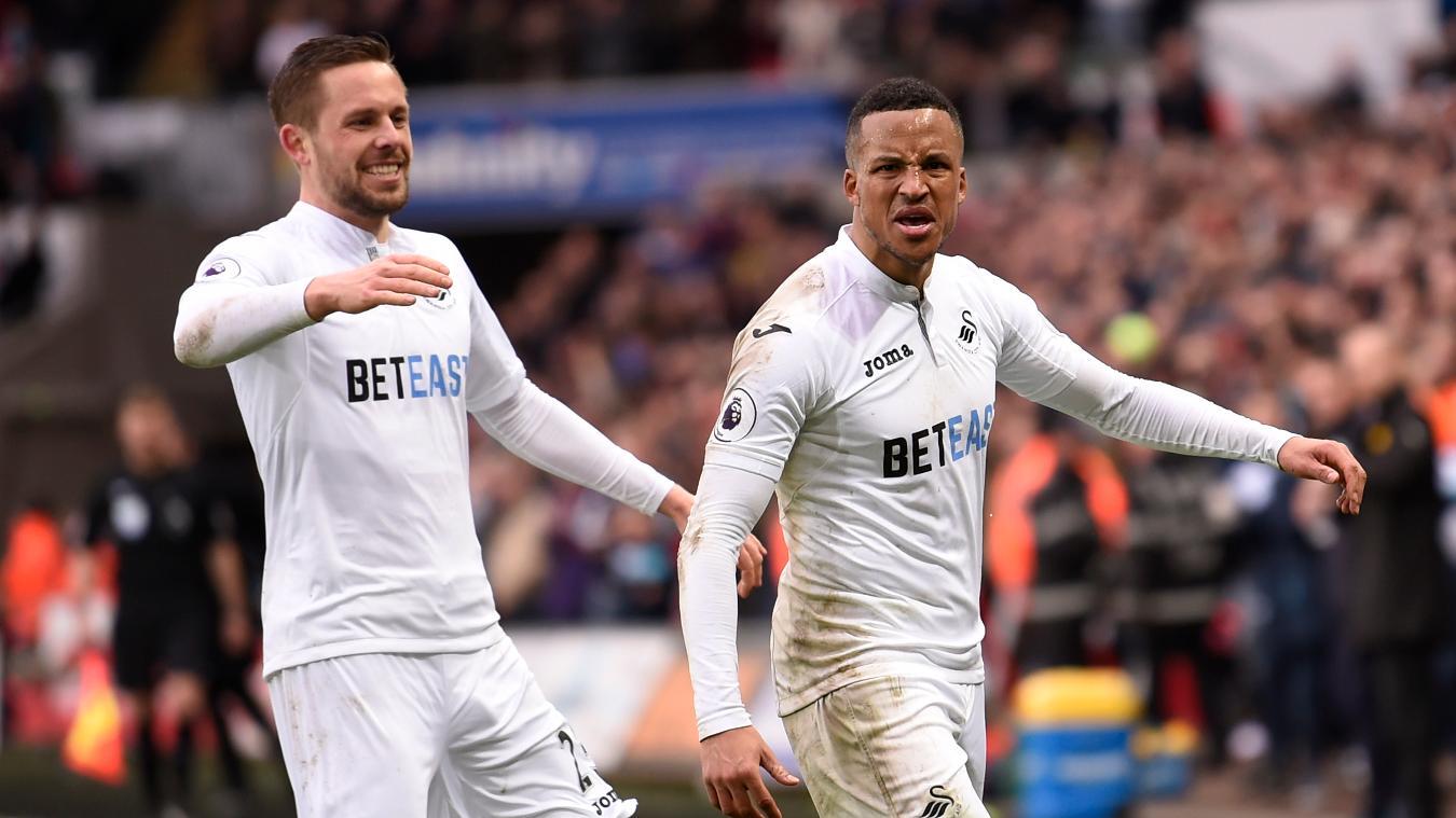 Swansea City's Martin Olsson celebrates scoring their second goal with Gylfi Sigurdsson (L)
