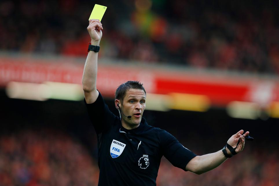 Referee Craig Pawson shows a yellow card