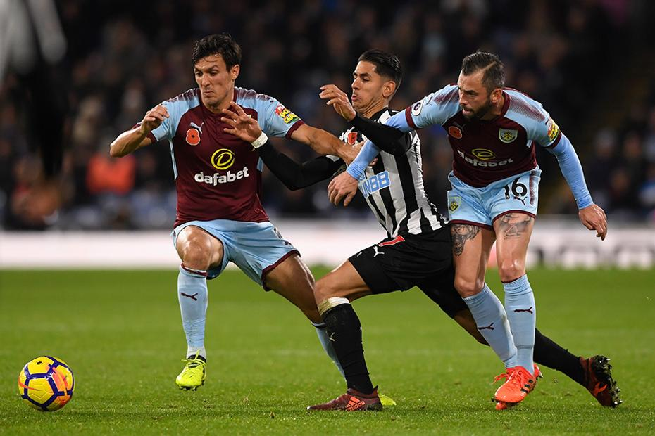 Burnley's Jack Cork and Steven Defour win the ball