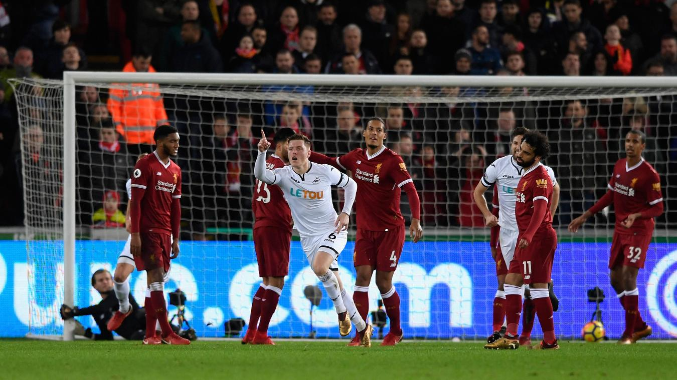 Alfie Mawson celebrates while Liverpool's players show their frustration and dejection
