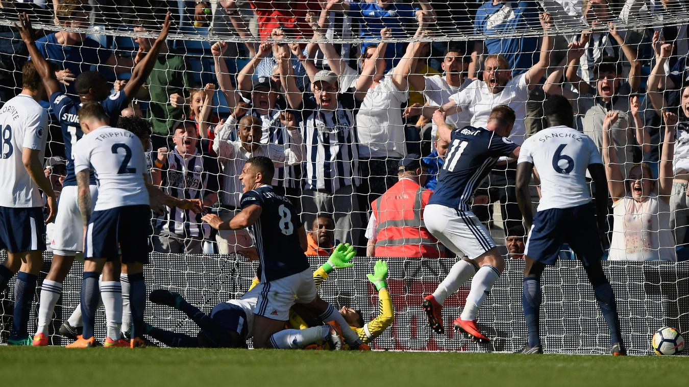 Albion's players and fans celebrate wildly as Jake Livermore, centre, bundles the ball into the net