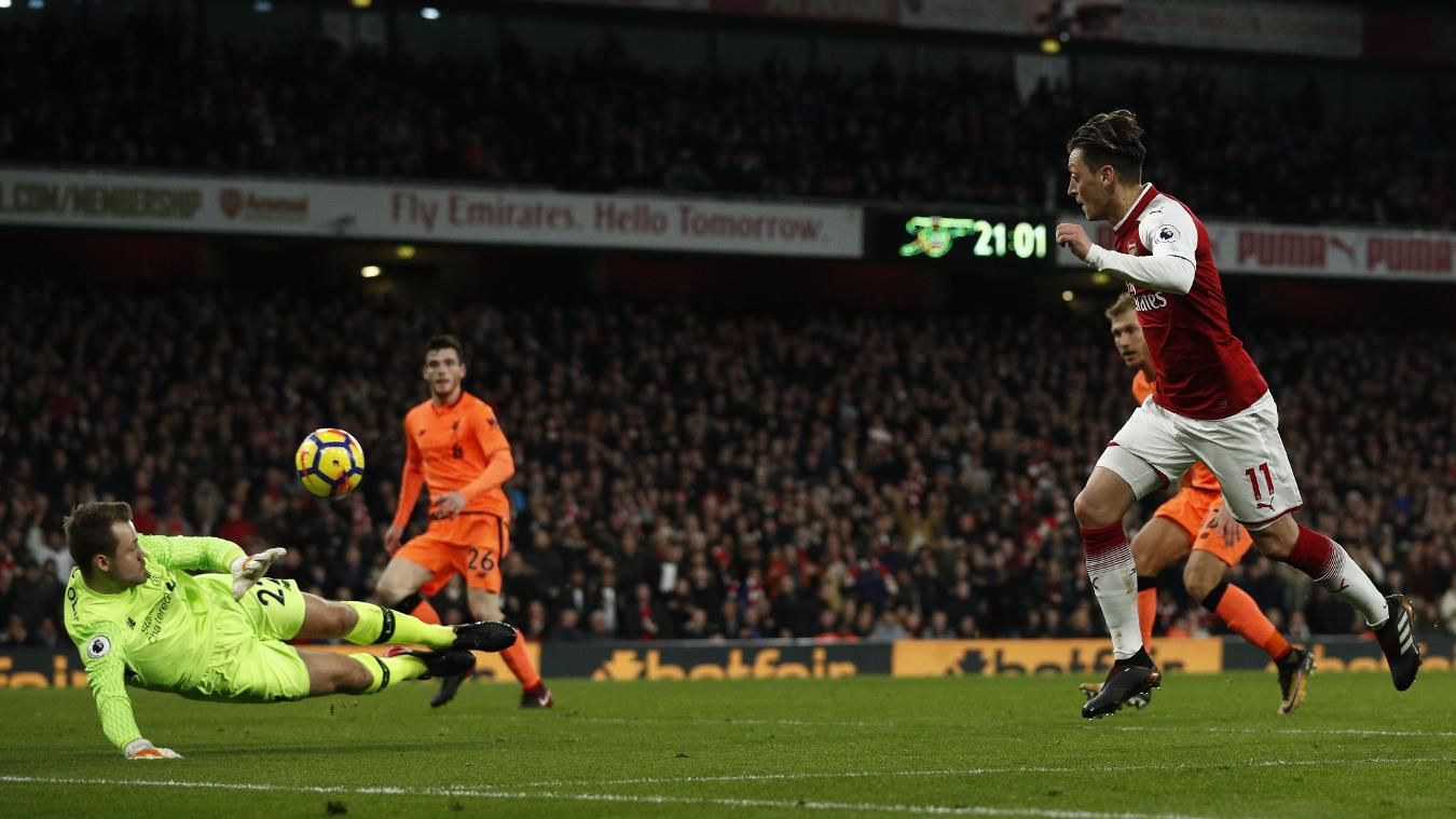 Mesut Ozil lifts the ball over Simon Mignolet as Arsenal score for the third time in five minutes