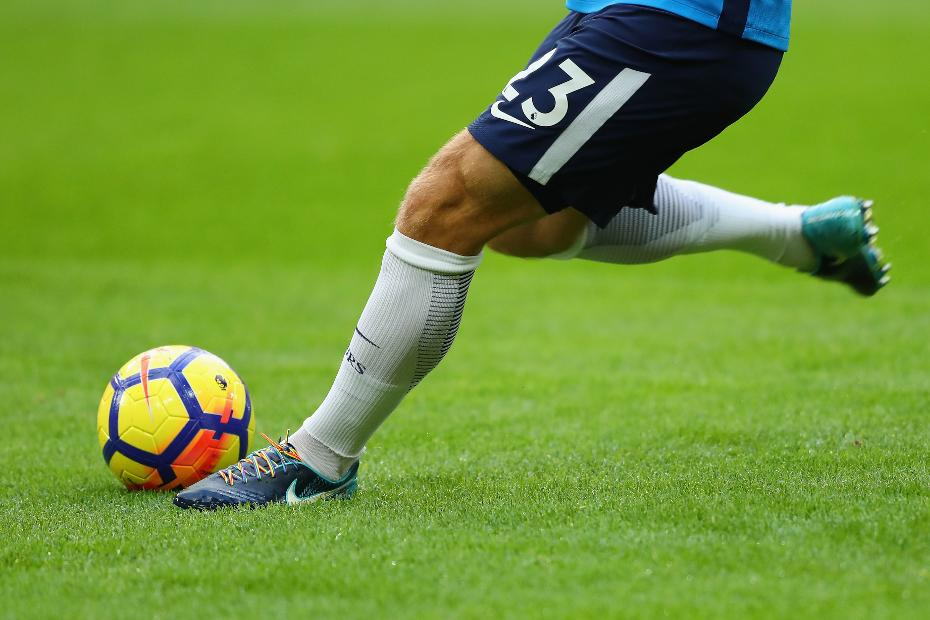 Player kicking ball with Rainbow Laces on boots